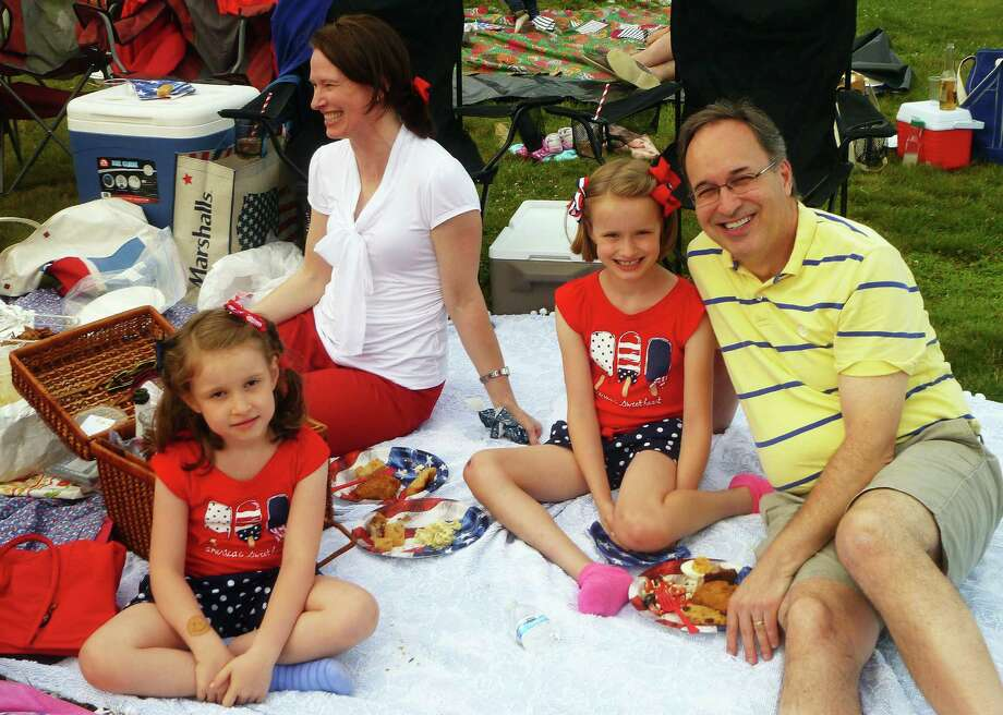 The Johnson family of Stamford enjoying a picnic at the New Canaan Family Fourth Celebration on Saturday, July 4, 2015. From left to right, Kate, 6, Julia Johnson, Bess, 8, and Scott Johnson. Photo: Martin Cassidy / Hearst Connecticut Media / New Canaan News