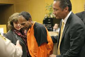 Francisco Sanchez, center, is lead out of the courtroom by San Francisco Public Defender Jeff Adachi, right, and a Spanish language interpreter (left), after his arraignment at the Hall of Justice on Tuesday, July 7, 2015,  in San Francisco. Prosecutors have charged the Mexican immigrant with murder in the waterfront shooting death of 32-year-old Kathryn Steinle.  (Michael Macor/San Francisco Chronicle via AP, Pool)