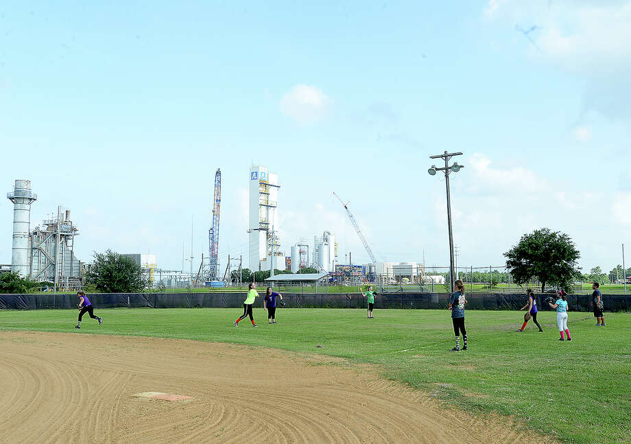 Members of the Port Neches - Groves Softball League state champions practice on their little league field Tuesday night. A development company looking to build on the open land off Merriman Road has raised concerns that the teams will lose their home fields, though the district's superintendent has said that there are no plans to tear down the fields.