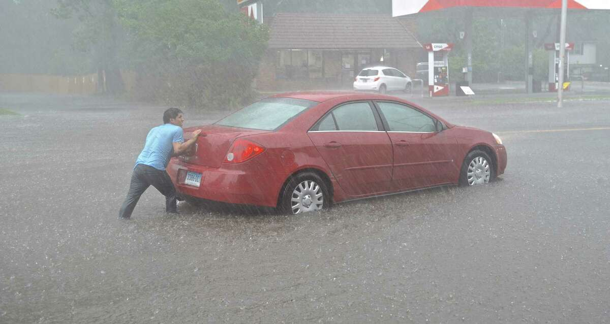 Daniel Pachezo, of Danbury, tries to push his car out of a flooded area of Main Street in Danbury, Conn, on Tuesday, July 7, 2015. pachezo drove into the area and his car stalled.
