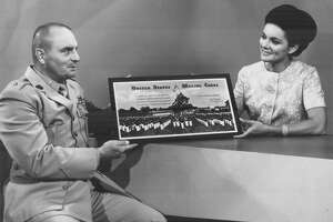 In this 1969 photo, Lt. Col. Fredrick McEwan presents an award of appreciation from the U.S. Marine Corps to Martha Buchanan, host of WOAI-TV's Early Evening Report, for her assistance in acquiring clothing and baby bottles for a Vietnamese orphanage.