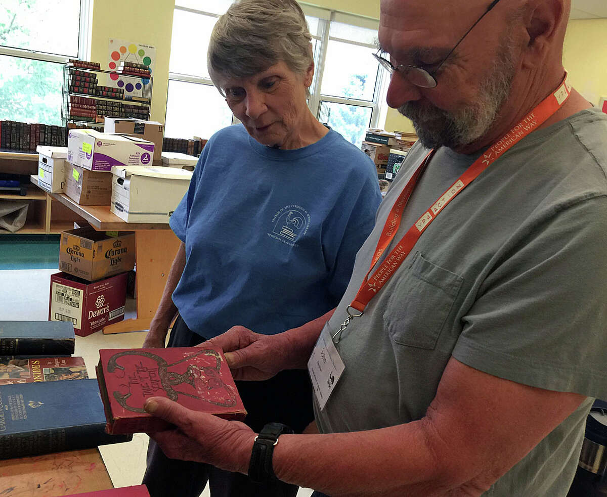 Rare book specialist John Renjilian and Joanne Zang, who founded the annual Booth Library book sale 40 years ago, preparing for 5-day event, which begins on Saturday at Reed Intermediate School.