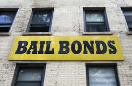 In this photo taken Tuesday, July 7, 2015, a bail bonds sign hangs on the side of a bail bonds business near Brooklyn's courthouse complex and jail in New York. Officials say they're eliminating cash bail for thousands of New Yorkers accused of misdemeanor and non-violent felonies in an effort to divert them from the Rikers Island jail complex. An $18 million plan to be unveiled Wednesday, July 8, will allow judges to instead require that people accused of certain crimes be monitored while they wait for their trial.