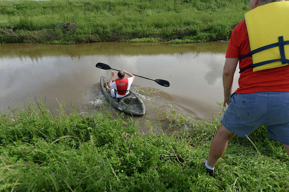 Chad Myzell, a kayaking enthusiast, slides his kayak into Willow Marsh Bayou near the Ben Rogers Visitors Center Monday afternoon. Myzell is leading an effort to attract a grant from the Texas Parks and Wildlife Department to build a kayak launch at the site. The project would attract other kayakers and help connect the bayou systems to other nature trails in the area. The bayou provides an ideal environment for kayaking in particular and allows one to be immersed in nature within less than a mile from the proposed put-in spot just off of Interstate 10.  Photo taken Monday, April 6, 2015 Kim Brent/The Enterprise Photo: Kim Brent / Beaumont Enterprise