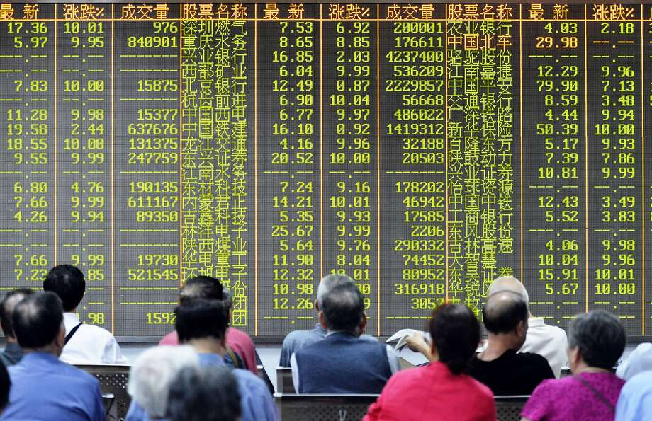 Investors sit in front of a screen showing market movements in a stock firm in Hangzhou, in eastern China's Zhejiang province. Photo: Str, AFP / Getty Images