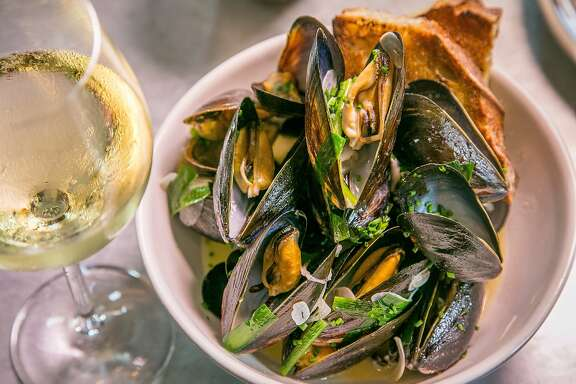 The pan roasted Mussels with a glass of white wine at Belga in San Francisco, Calif., is seen on July 7th, 2015.