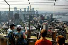 Onlookers struggle to enjoy the view through a haze hanging over Seattle's skyline; a result of wildfires burning northeast of Whistler, B.C. Photographed Wednesday, July 8, 2015, as seen from the top of the Space Needle in Seattle, Washington.