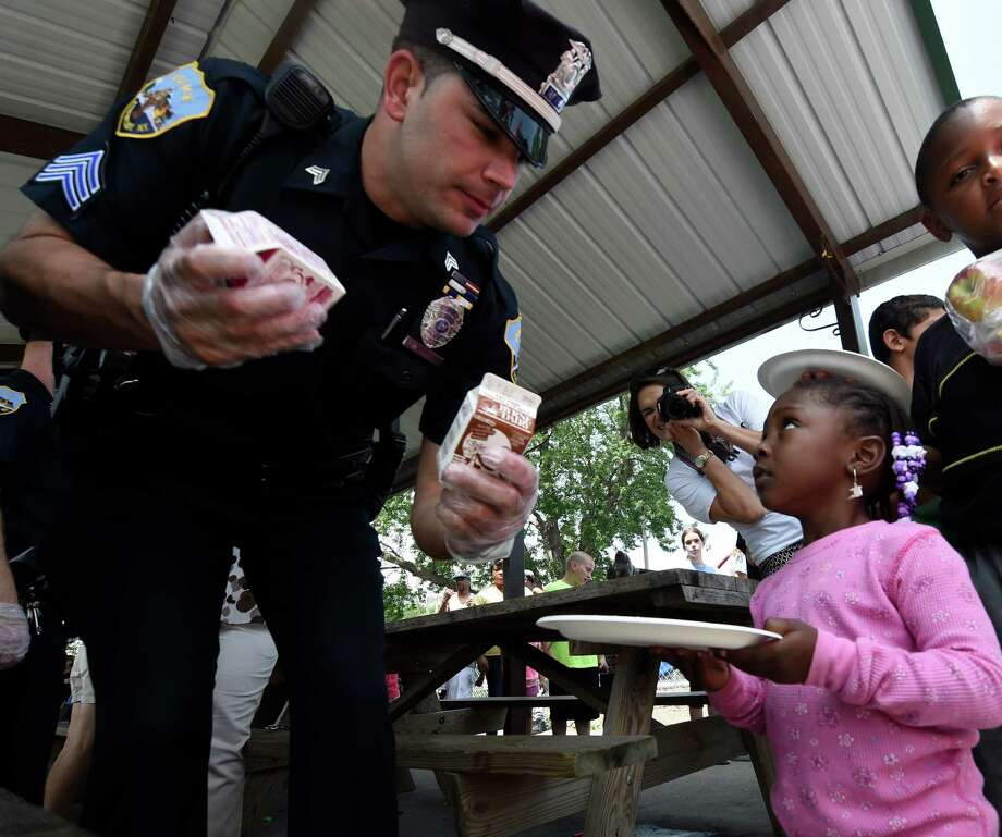 Schenectady police Sargent Jeffrey McCutcheon serves lunch to Trinity Grace, 3, at Jerry Burrell Park Wednesday afternoon, July 8, 2015, during the Free Summer Lunch program Kickoff event hosted by the Schenectady Inner City Ministry in Schenectady, N.Y.     (Skip Dickstein/Times Union) Photo: SKIP DICKSTEIN / 00032338A