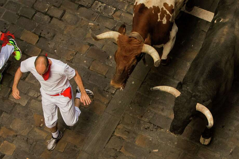 El Tajo y La Reina fighting bull, right, and a steer, centre, run after revelers during the running of the bulls, at the San Fermin festival, in Pamplona, Spain, Wednesday, July 8, 2015. Revelers from around the world arrive in Pamplona every year to take part in some of the eight days of the running of the bulls.  Photo: Andres Kudacki, Associated Press / AP