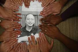 Ecology Center store and office staff place their hands along the border of a portrait of Daniel Maher on Wednesday, July 8, 2015 in Berkeley, Calif. Maher, who has been director of the recycling program at the Ecology Center in Berkeley for nearly 10 years is being deported for a felony crime he committed two decades ago.