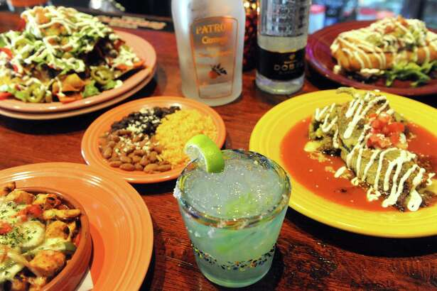 A jalapeno margarita, center, surrounded by, from left clockwise, pollo Azteca, rice and beans, ball park nachos, chile rellenos and chimichanga at Mexican Radio on Thursday July 2, 2015 in Schenectady, N.Y. (Michael P. Farrell/Times Union)
