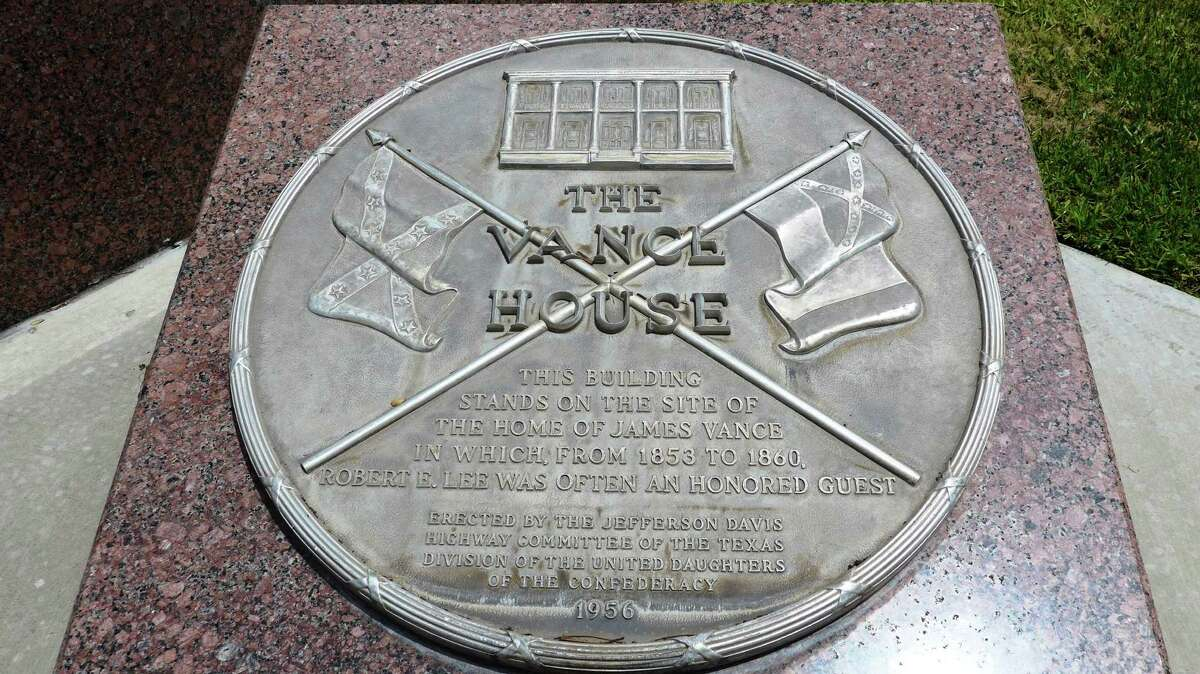 A 1956 marker at the site of the Vance House, which notes that Robert E. Lee was a frequent guest from 1853-60, includes images of two Confederate flags. Shown Wednesday, July 8, 2015, the marker is located on county property, across the street from the Bexar County Courthouse, at the former site of the Federal Reserve Bank building on West Nueva Street.