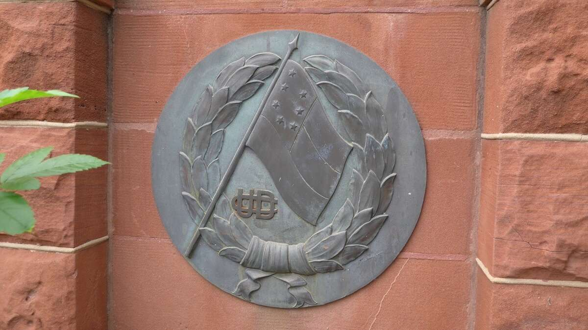 A plaque outside the Bexar County Courthouse, showing a seven-star Confederate flag and the initials of the United Daughters of the Confederacy, are part of a monument marking San Antonio as part of the Jefferson Davis Memorial Highway. It was dedicated in 1936 to the soldiers of the Confederacy and Daughters of the Confederacy.
