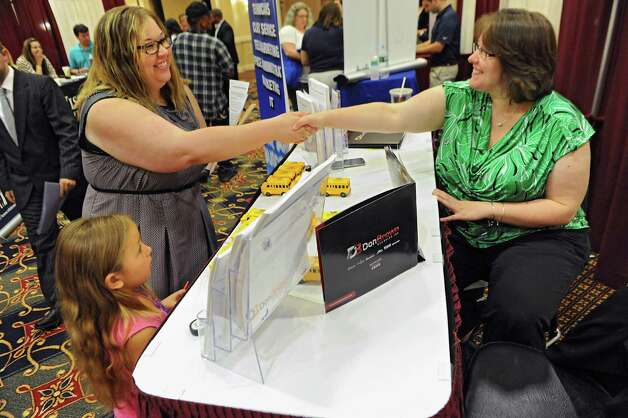 Alicia Stealey of Amsterdam who came with her daughter Kaydence, 7, shakes hands with Tonya Harris, human resources director for Don Brown Bus Sales, Inc., during the Times Union job fair at the Albany Marriott Hotel on Wednesday, July 8, 2015 in Colonie, N.Y.  (Lori Van Buren / Times Union) Photo: Lori Van Buren / 00032511A