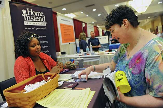 Jonell Thomas, recruitment coordinator for Home Instead Senior Care, talks to Rebecca Dykeman of Schenectady, right, during the Times Union job fair at the Albany Marriott Hotel on Wednesday, July 8, 2015 in Colonie, N.Y.  (Lori Van Buren / Times Union) Photo: Lori Van Buren / 00032511A
