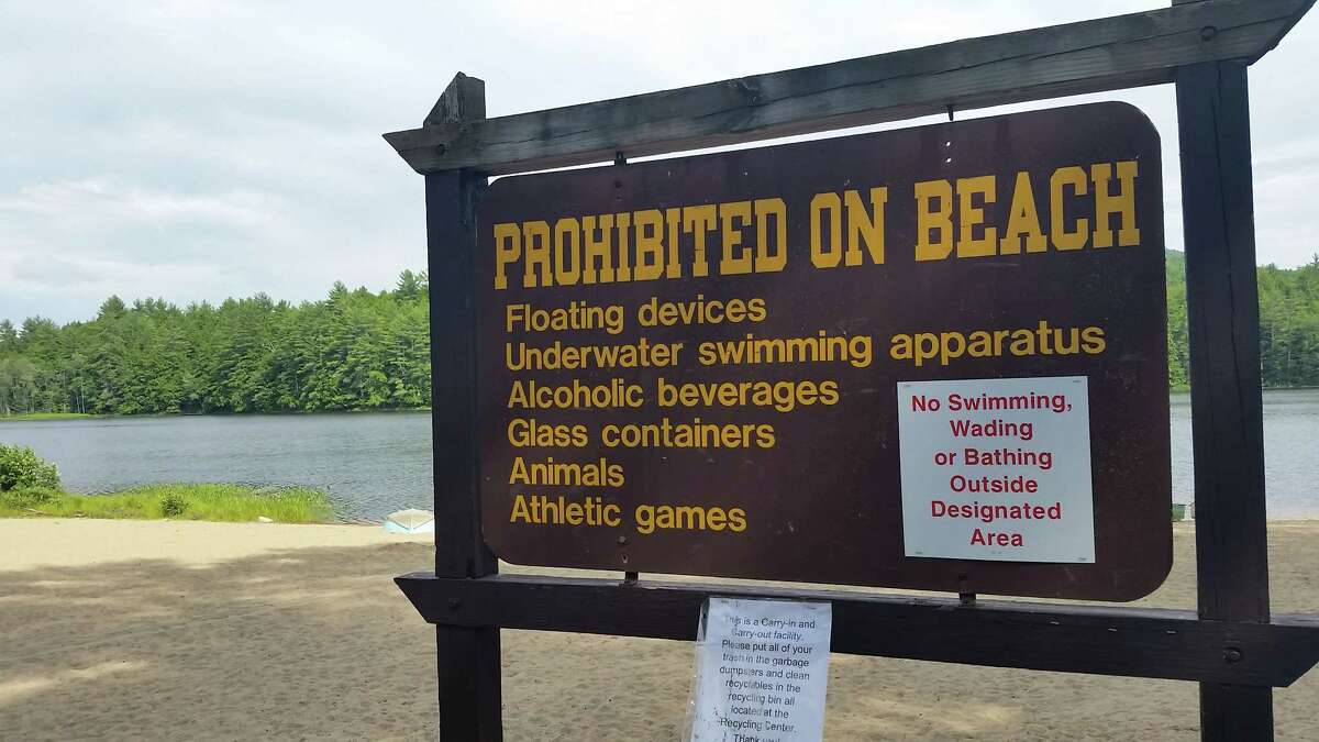 A sign at the empty beach along Fourth Lake at the Luzerne Campground in Lake Luzerne. Swimming at the beach is prohibited because the state has been unable to find a lifeguard. (Photo by Chris Churchill / Times Union)