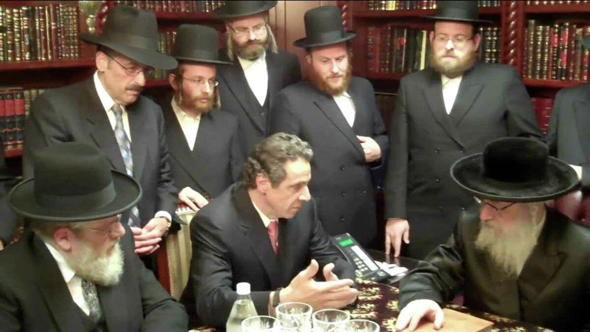 Screen grab taken from Youtube showing Abraham Eisner, upper left corner, standing behind Gov. Andrew Cuomo during a meeting with Rabbi Asher Anshel Katz on Oct. 3, 2010, in the Williamsburg neighborhood of Brooklyn, N.Y.