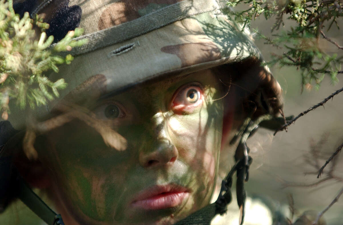 U.S. Army medic Pvt. Sadie Dodd peers through bushes in searh of enemy fighters during a platoon march during a training course for combat medics at Camp Bullis north of San Antonio on December 11, 2002. The medics came under fire and had to establish a security perimeter, stablized the wounded and evacuate them to an ambulance. ( Joshua Trujillo / Staff )