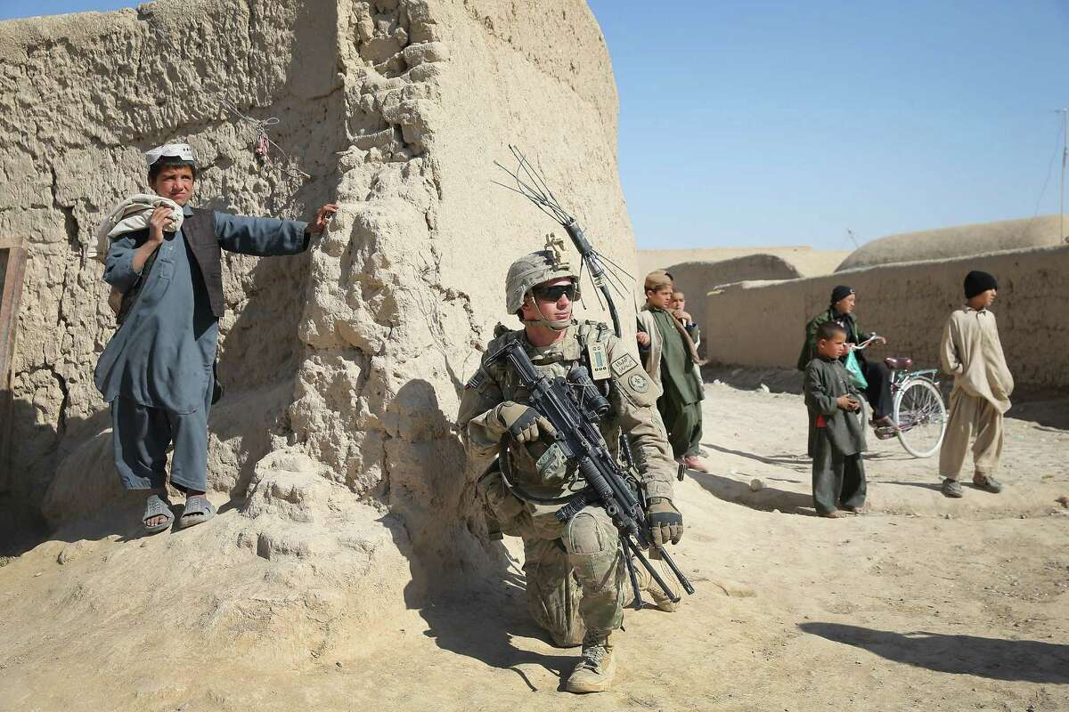 KANDAHAR, AFGHANISTAN - FEBRUARY 27: PFC Jason Rajabi from Charleston, South Carolina with the U.S. Army's 4th squadron 2d Cavalry Regiment keeps watch during a patrol in a village on February 27, 2014 near Kandahar, Afghanistan. Defense Secretary Chuck Hagel announced recently he is making preparations for a complete military withdrawal from Afghanistan because Afghanistan President Hamid Karzai continues to refuse to sign the Bilateral Security Agreement. Fourth squadron 2d Cavalry Regiment is responsible for defending Kandahar Airfield against rocket attacks from insurgents. (Photo by Scott Olson/Getty Images) *** BESTPIX ***
