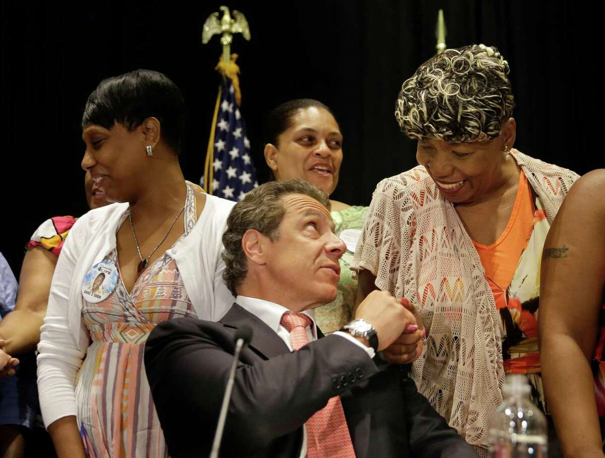 Surrounded by women whose family members were killed by police officers, New York Governor Andrew Cuomo, center, greets Gwen Carr, mother of Eric Garner, after Cuomo signed an executive order in New York, Wednesday, July 8, 2015. New York's governor has issued an executive order that puts the office of the state attorney general in charge of investigating killings by police. (AP Photo/Seth Wenig) ORG XMIT: NYSW125