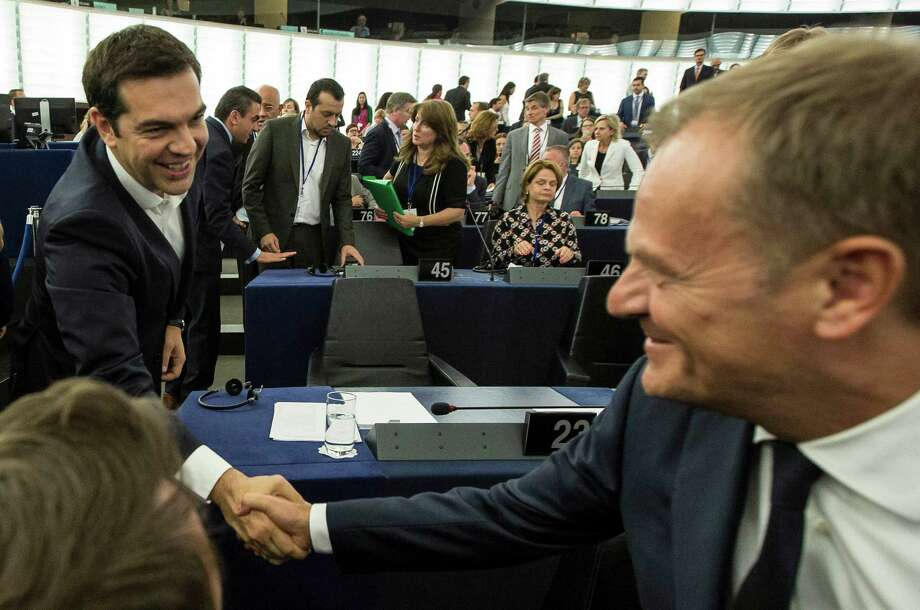 Greek Prime Minister Alexis Tsipras, left, shakes hands with Donald Tusk, president of the European Council, before delivering his speech at the European Parliament in Strasbourg, eastern France, Wednesday, July 8, 2015.  Tsipras says his country wants a deal that will mean a definitive end to Greece's protracted financial crisis, and that last Sunday's referendum result does not mean a break with Europe. (AP Photo/Jean-Francois Badias) ORG XMIT: PAR102 Photo: Jean-Francois Badias / AP