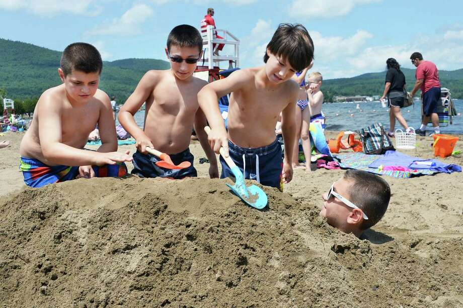 Nine-year-old Jake Lanning, right, is buried in the sand by, from left, Anthony Lanning, 12, Jonathan Failla, 12, and Matthew Failla, all of LongIsland, at Million Dollar Beach Wednesday July 8, 2015 in Lake George, NY.  (John Carl D'Annibale / Times Union) Photo: John Carl D'Annibale