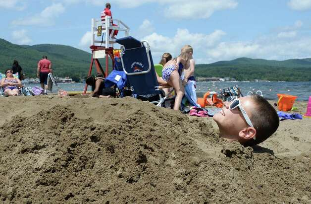 Nine-year-old Jake Lanning of Oceanside is buried in the sand on Million Dollar Beach Wednesday July 8, 2015 in Lake George, NY.  (John Carl D'Annibale / Times Union) Photo: John Carl D'Annibale