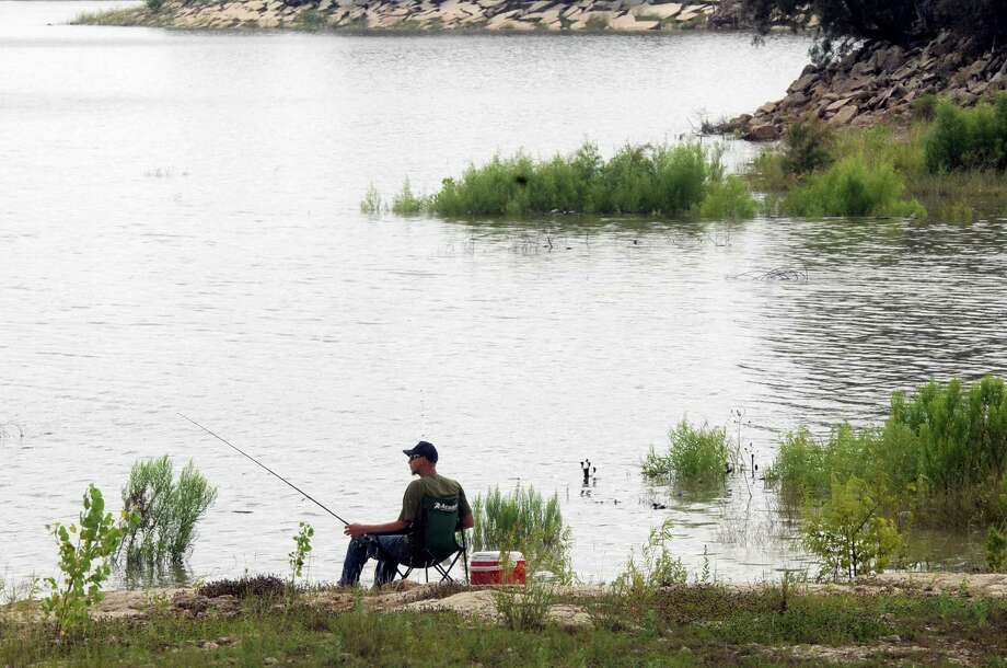 A man fishes in high water on Fort Phantom Hill Lake on Wednesday after a record day of rain in Abilene, which was on alert for flash flooding. See the  forecast for the Houston area on Page B10. Photo: Nellie Doneva, MBR / The Abilene Reporter-News