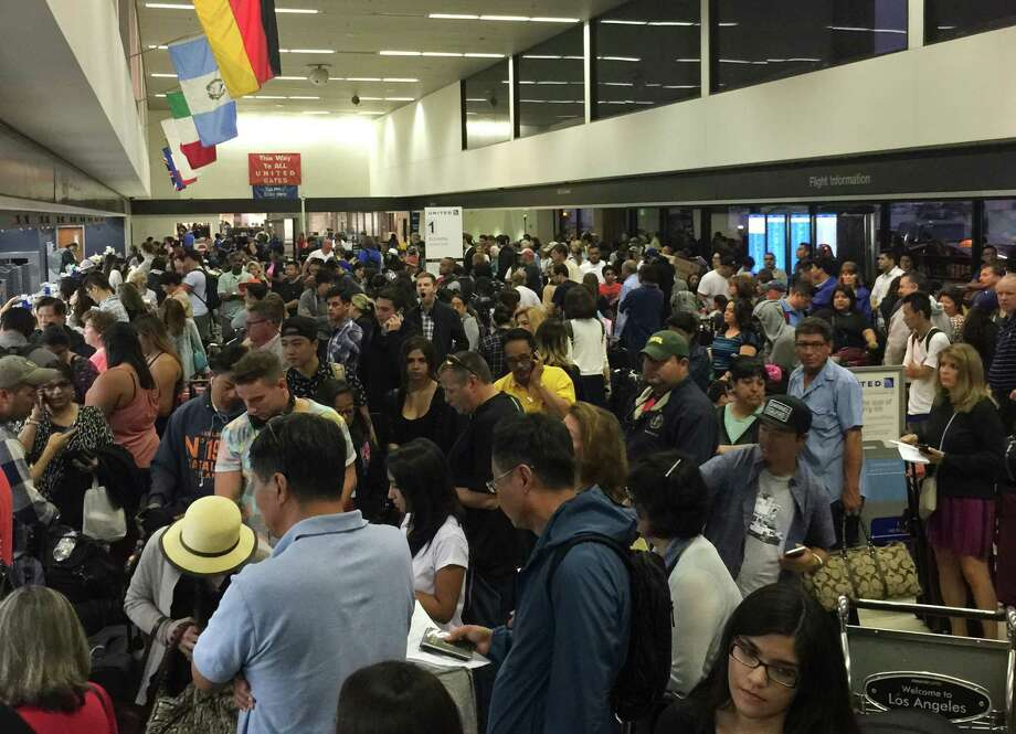 People gather at Los Angeles International Airport as United Airlines experienced computer problems in Los Angeles, Wednesday, July 8, 2015. A United spokeswoman said that the glitch was caused by an internal technology issue and not an outside threat or hacker. (Aristomenis Tsirbas via AP) Photo: Aristomenis Tsirbas, UGC / Aristomenis Tsirbas