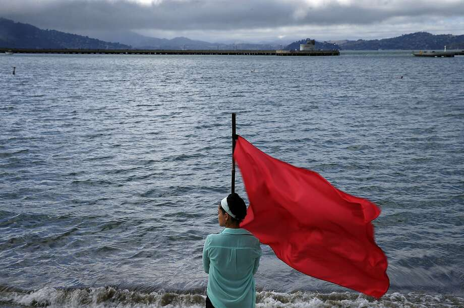 "Amelia Uzategui holds a flag as Inkboat performs ""95 Rituals"" starting on the Aquatic Park Beach before heading to the Eureka, a site specific tribute to Anna Halprin to honor her 95th birthday, at the Hyde Street Pier in San Francisco, Calif., on Wednesday, July 8, 2015. Photo: Carlos Avila Gonzalez, The Chronicle"