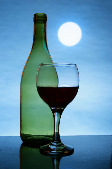 Still life with bottle and glass of red wine, full moon in the background Photo: Roman Sigaev / handout / stock agency