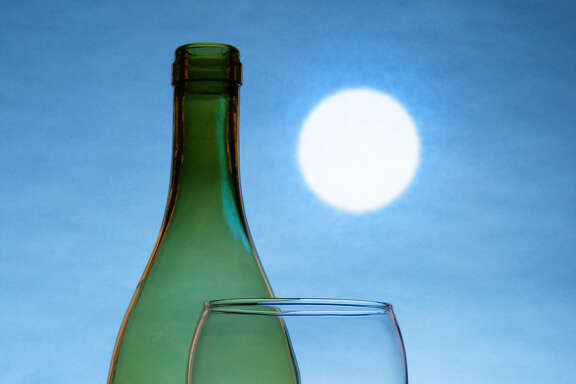 Still life with bottle and glass of red wine, full moon in the background