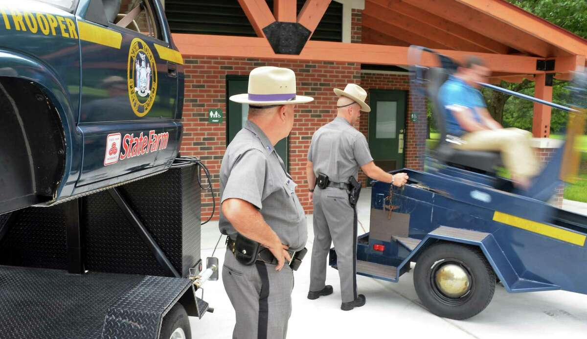 """New York State Troopers operate the 'seatbelt convincer,"""" right, during a news conference to encourage visitors to our State's parks to buckle up for safety Thursday, July 9, 2015, at Saratoga Spa State Park in Saratoga Springs, N.Y. (John Carl D'Annibale / Times Union)"""