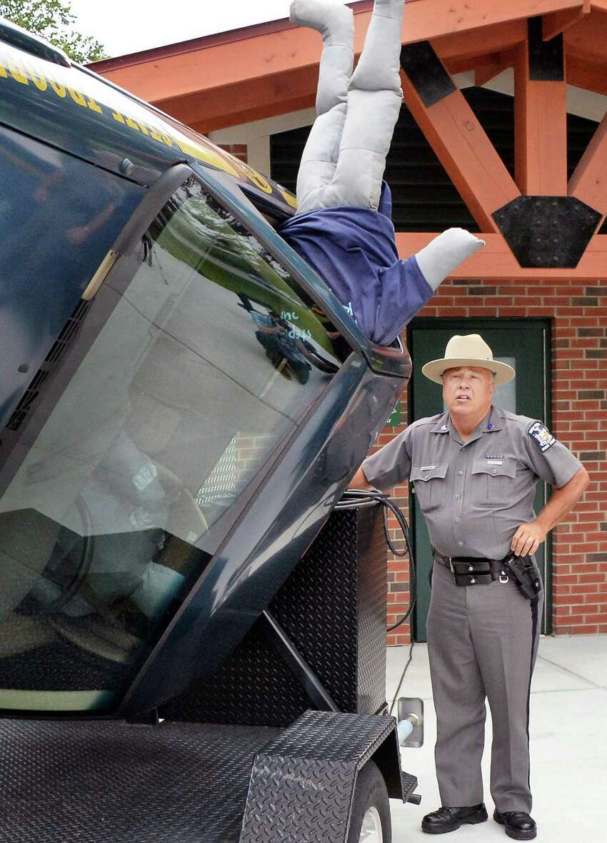 New York State Trooper Mike Anson watches as a crash dummy, not wearing his seatbelt, is tossed from rollover simulator during a news conference to encourage visitors to our State's parks to buckle up for safety Thursday, July 9, 2015, at Saratoga Spa State Park in Saratoga Springs, N.Y. (John Carl D'Annibale / Times Union)