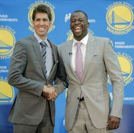 Warriors player Draymond Green (right) and general manager Bob Myers pose for a photo at a press conference held to announce the re-signing of Green at the Warriors team practice facility in Oakland, California, on Thursday, July 9, 2015. Green was signed out of free agency to a multi-year contract. Per team policy, terms of the agreement were not announced.