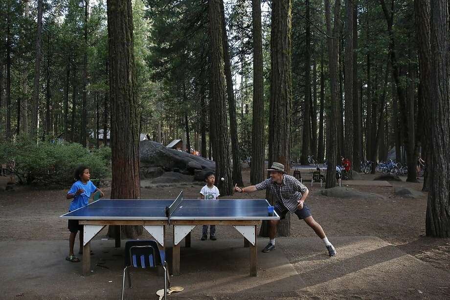 Chemnui Simpson, 8, left, plays ping-pong against Kyle Macdonald as Jacob Tom, 6, watches the match at Camp Mather. Photo: Leah Millis, The Chronicle