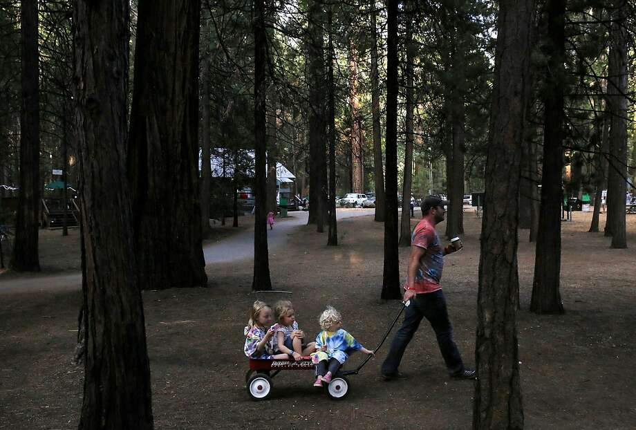 From left, Ava Goldenberg, 5, Kaitlyn Cleaveland, 4, and Joseph Goldenberg, 2, are pulled to an evening movie by David Goldenberg July 8, 2015 at Mather Family Camp in Groveland, Calif. The California State Water Board's curtailment notice served to San Francisco Public Utilities Commission could affect the water supply at the popular San Francisco family summer camp. Photo: Leah Millis, The Chronicle