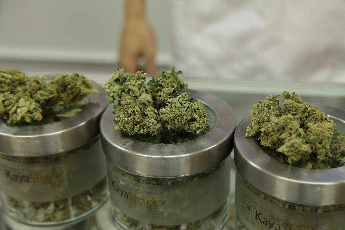 An employee at the medical marijuana dispensary displays different types of marijuana flowers. On Friday morning, woman delivering marijuana in San Francisco was robbed and carjacked in the city's Excelsior District (AP Photo/Gosia Wozniacka).