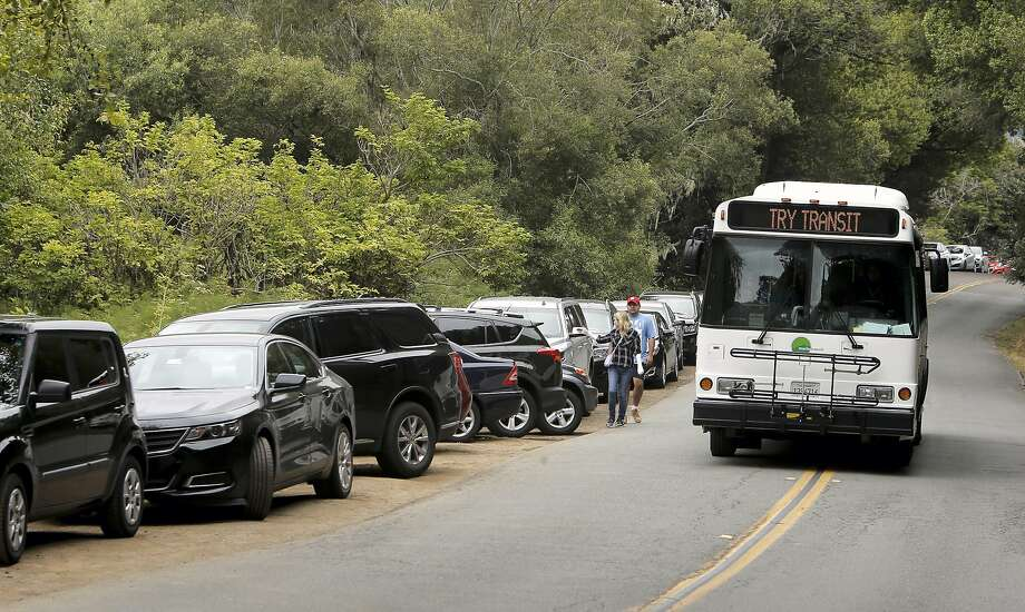 A Marin Transit bus displays a suggestion as it passes lines of parked cars along Muir Woods Road, near Muir Woods National Park, in Mill Valley, Calif. where parking is always challenging as seen on Thurs. July 9, 2015, Photo: Michael Macor, The Chronicle