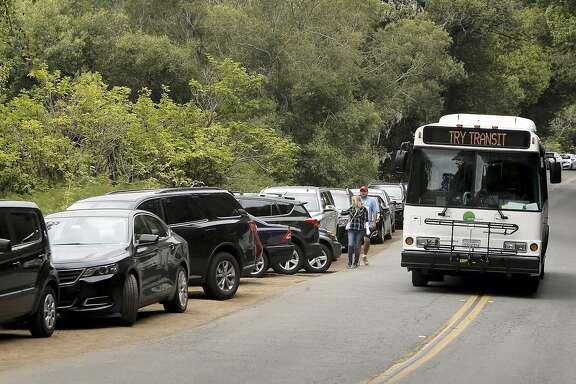 A Marin Transit bus displays a suggestion as it passes lines of parked cars along Muir Woods Road, near Muir Woods National Park, in Mill Valley, Calif. where parking is always challenging as seen on Thurs. July 9, 2015,