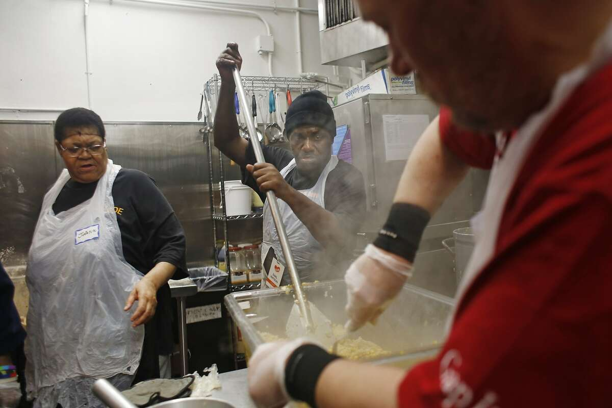 Cook Earl Watson (center) stirs rice for the lunch meal service as he, Joann Adams (left), cook, and Bill Sischo (right), staff, help prepare it for the lunch meal service at Glide Memorial on Thursday, July 9, 2015 in San Francisco, Calif.