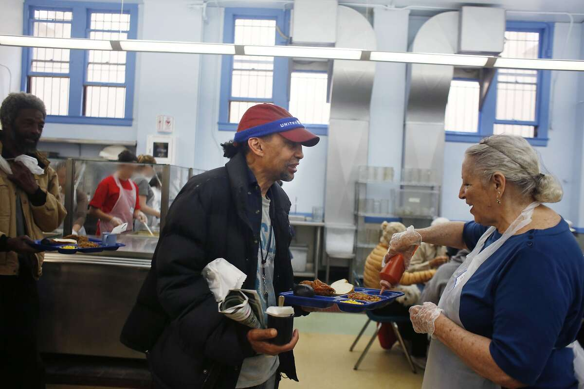 Theodore Sparks (l to r) talks with Sue Applebaum, volunteer, as she adds hot sauce to his fried chicken in the newly painted dining room during the lunch meal service at Glide Memorial on Thursday, July 9, 2015 in San Francisco, Calif.