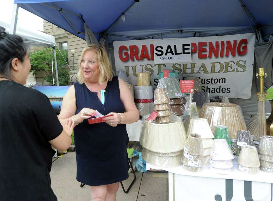 At right, Bonnie Engelson of Just Shades hands a business card to a shopper during the Greenwich Chamber of Commerce sponsored event, Sidewalk Sale Days, on Greenwich Avenue and the surrounding business district, Thursday, July 9, 2015. Photo: Bob Luckey Jr. / Hearst Connecticut Media / Greenwich Time