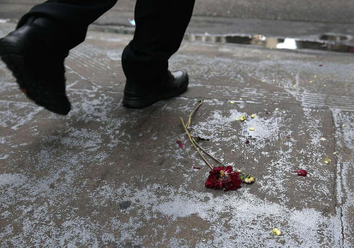 A man walking on Sutter Street avoids a flattened flower on the sidewalk in downtown San Francisco, Calif. on Thursday, July 9, 2015.