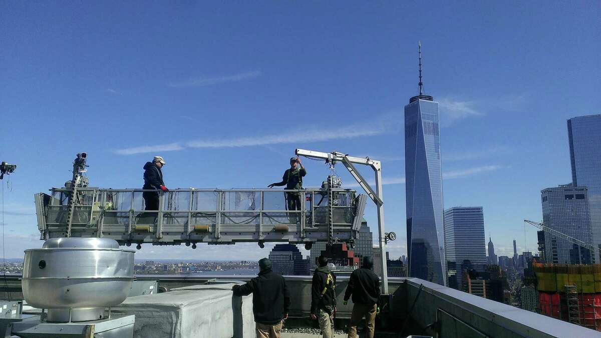 With New York City's Freedom Tower as a backdrop, workers with Stamford, Conn.-based Sentinel Maintenance prepare to clean windows at the Ritz-Carlton New York, Battery Park.