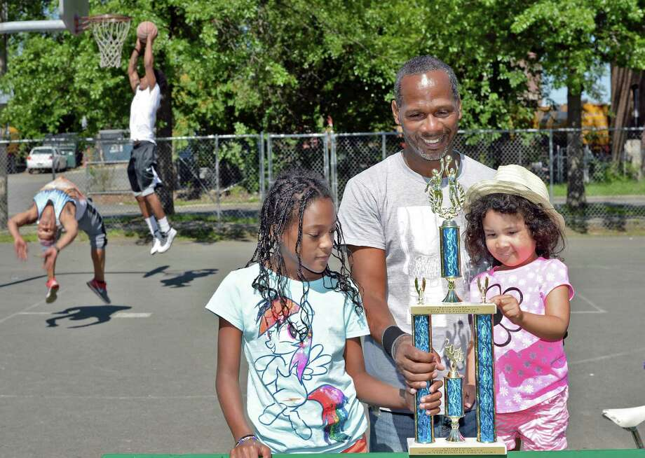 Kevin Pryor shows daughter Jordan Pryor, 10, and granddaughter Kamiila Pryor-Phillips, 3, right, the winner's trophy for his basketball tournament for kids on the Fourth of July at the Seventh Avenue park Friday July 3, 2015 in Troy, NY.  (John Carl D'Annibale / Times Union) Photo: John Carl D'Annibale / 00032468A