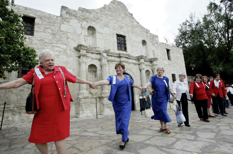 In this Oct. 5, 2006, file photo, members of the Daughters of the Republic of Texas join hands as they circle the Alamo in San Antonio as they mark their 100th anniversary of custodianship of the Alamo. A foundation that had planned to create a $400 million endowment to help the Alamo has disbanded within a year of announcing its plans. The foundation was technically separate from but endorsed by the Daughters of the Republic of Texas, a century-old group that oversees the historic Alamo grounds in downtown San Antonio. (AP Photo/Eric Gay, File) Photo: ERIC GAY, STF / AP / AP2005