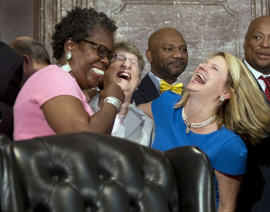 Rep. Gilda Cobb-Hunter, D-Orangeburg, left, laughs with South Carolina Supreme Court Chief Justice Jean Toal, center, and Rep. Jenny Horne, R-Summerville, before a ceremony where South Carolina Gov. Nikki Haley signed a bill into law, Thursday, July 9, 2015, at the Statehouse in Columbia, S.C. The law enables the removal of the Confederate flag from the Statehouse grounds more than 50 years after the rebel banner was raised to protest the civil rights movement. (AP Photo/John Bazemore) Photo: John Bazemore, Associated Press