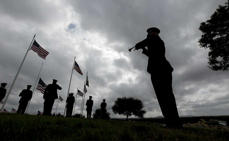 A rifle squad fires a salute at the conclusion of the ceremony as a bugler plays taps for Army Sgt. Charles Schroeter, who was awarded the Congressional Medal of Honor for gallantry in an 1869 battle during the Indian Wars, during a service with full military honors at Miramar National Cemetery, Thursday, July 9, 2015, in San Diego. Schroeter's remains were located only recently, when the Congressional Medal of Honor Historical Society traced them to San Diego's Greenwood Memorial Park, where they had rested since 1921.  The remains were interred in an unmarked crypt, along with other unclaimed remains. Photo: Chris Carlson, Associated Press