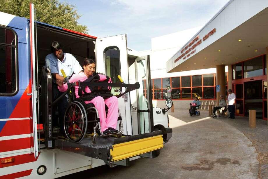A MetroLift driver, left, helps a passenger off a MetroLift bus upon arrival at the West Gray Multipurpose Center near Montrose. Photo: Brett Coomer, Houston Chronicle / © 2012 Houston Chronicle
